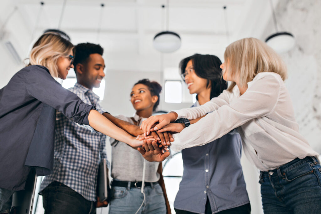 cheerful-international-students-with-happy-face-expression-going-to-work-together-on-science-project-indoor-photo-of-blonde-woman-in-trendy-blouse-holding-hands-with-coworkers-scal